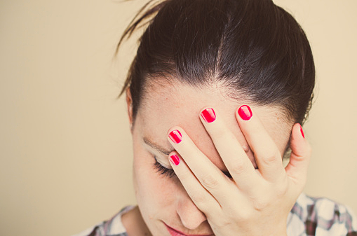 Tired or worried woman w/ hand on face